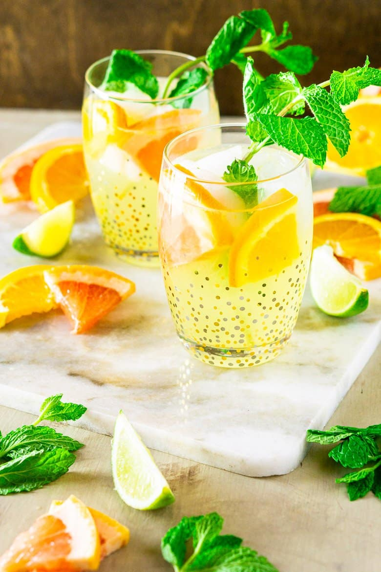 A triple citrus tequila smash with mint leaves and fruit around it.