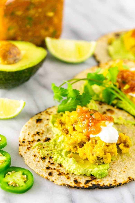 Three chorizo breakfast tacos with jalepnos, salsa and avocado.