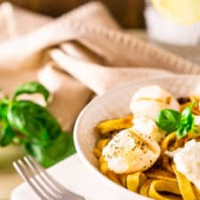 A bowl of grilled scallop pasta with fresh basil and a water with lemon in the background.
