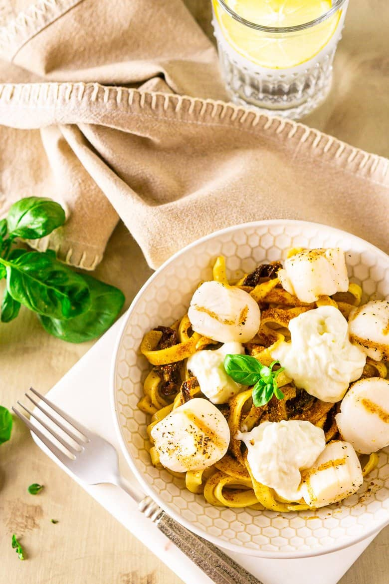 An aerial view of the grilled scallop pasta with fresh basil on the side.