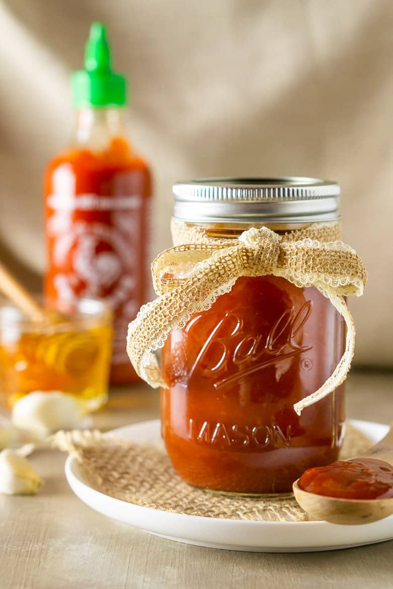A jar of honey-sriracha BBQ sauce with a burlap ribbon on a plate with a spoonful of sauce.
