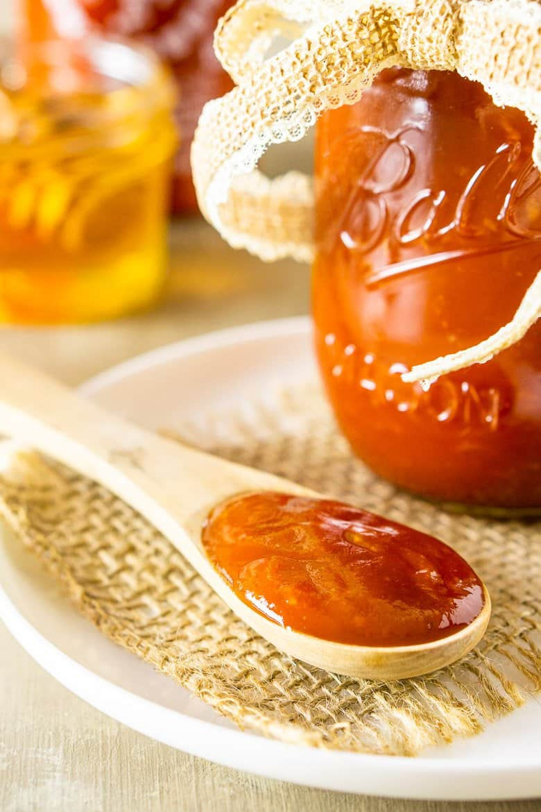 A wooden spoon with honey-sriracha BBQ sauce and a jar of sauce.