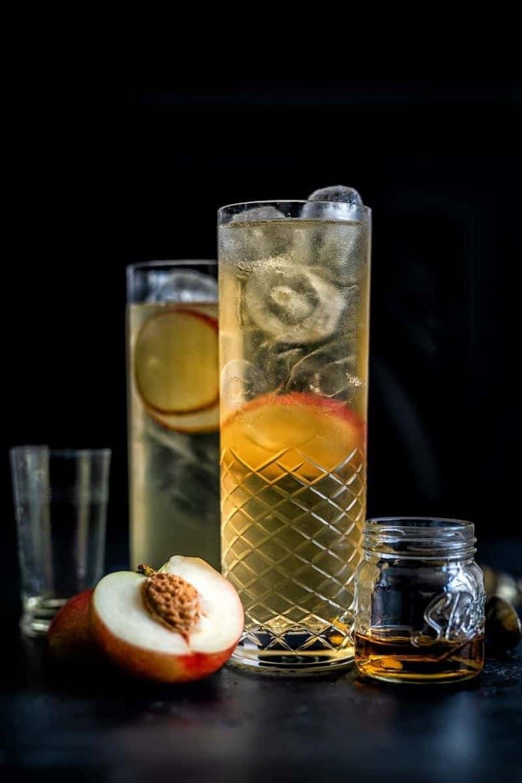 A fizzy peach whisky cocktail with a peach half.