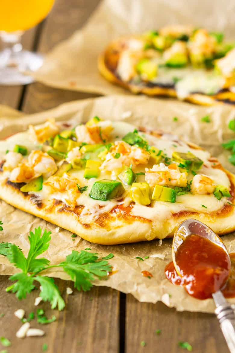 A shrimp and avocado grilled naan pizza on parchment paper with BBQ sauce.