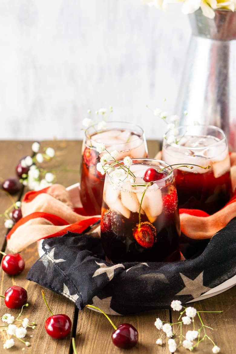 An aerial view of three cherry vodka cocktails on flag-themed cloth.