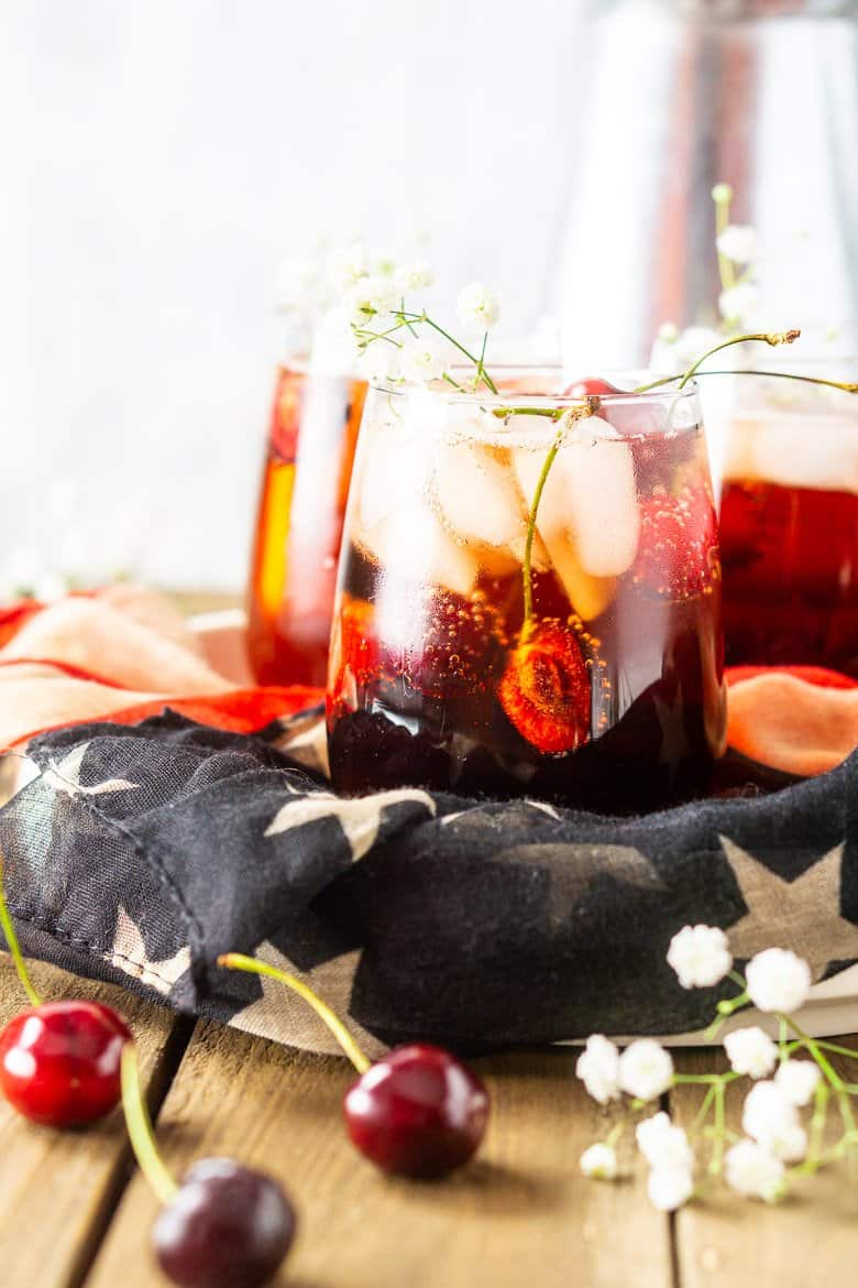 A close-up of one cherry vodka cocktail with flowers and fresh cherries.