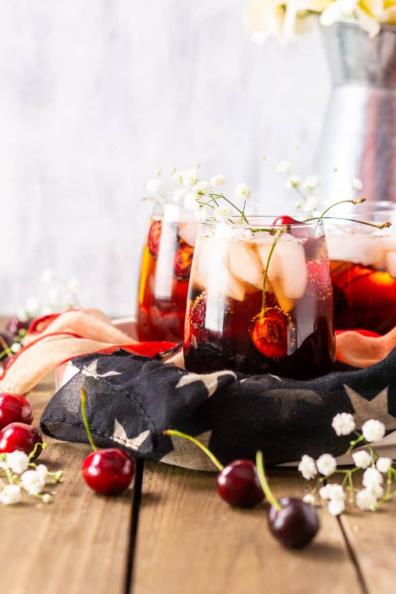 A straight-on view of three cherry vodka cocktails with a metal vase of flowers.