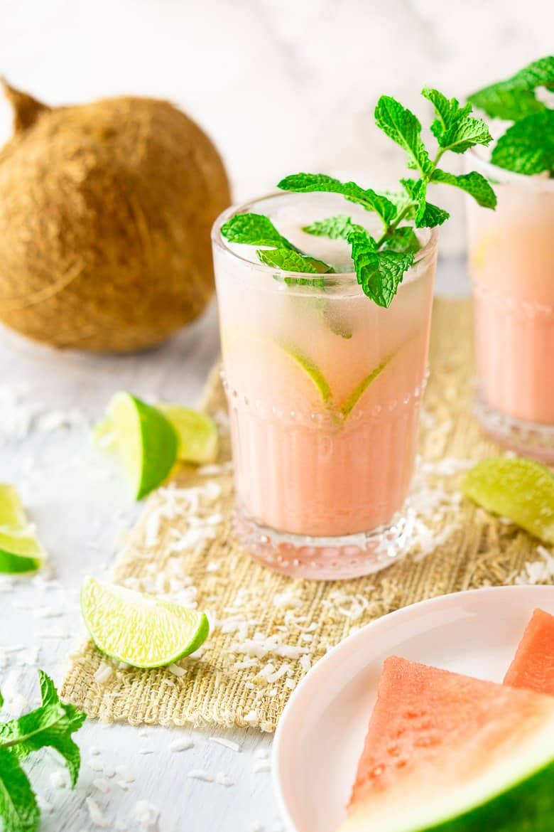 A coconut-watermelon mojito with mint leaves and lime slices.