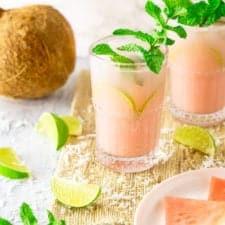 A coconut-watermelon mojito with a coconut and watermelon slices.