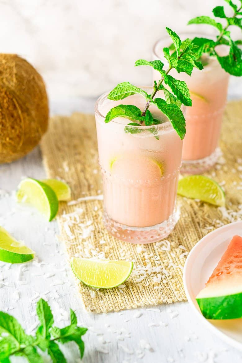 A side view of two coconut-watermelon mojitos.