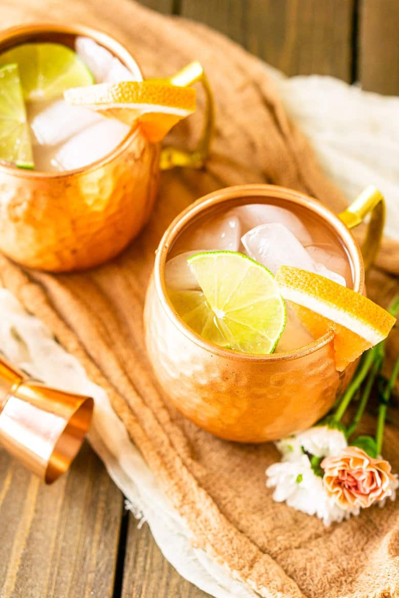 An aerial view of two grapefruit gin mules on cloth.