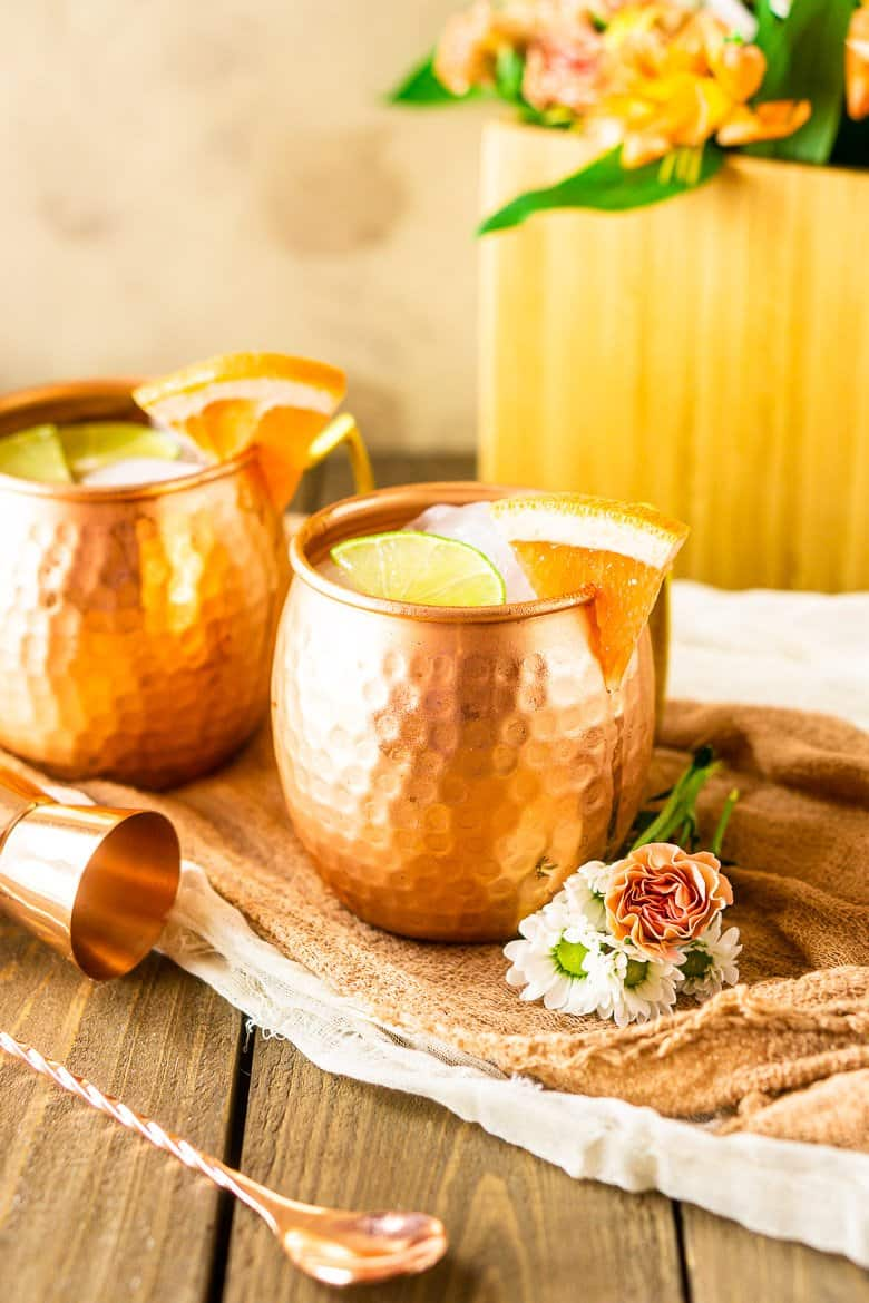 A grapefruit gin mule with flowers and copper barware.
