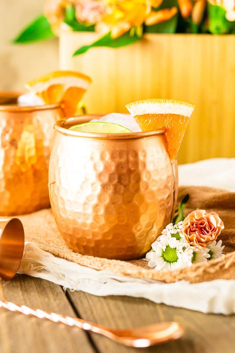 A grapefruit gin mule with a wooden box of flowers.