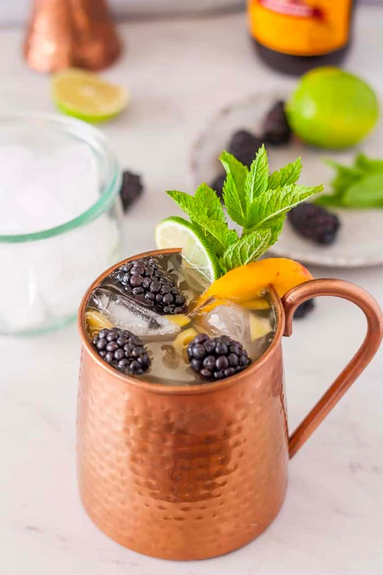 A peach Moscow mule with peaches and blackberries.