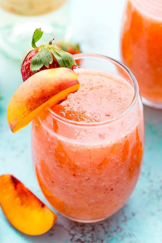 A strawberry peach white wine slushy with fresh fruit on the side.