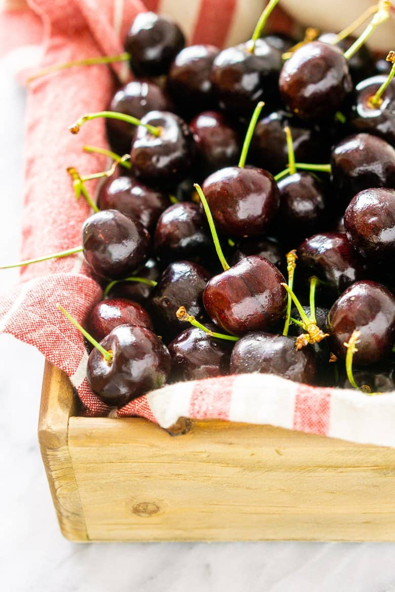 A wooden box filled with fresh cherries.