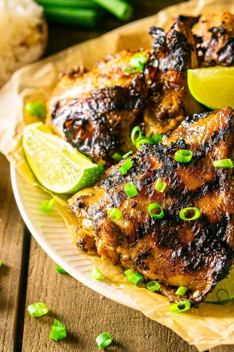 A close-up shot of a plate of grilled Jamaican jerk chicken.