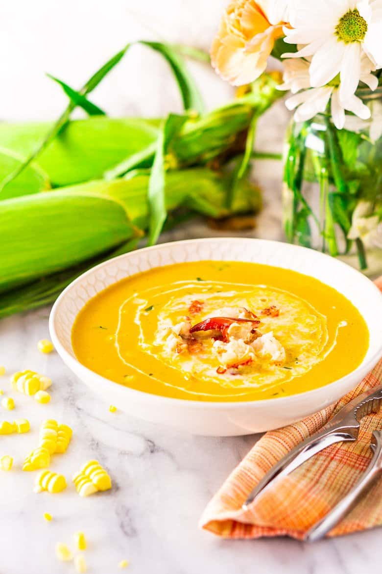 A bowl of summer herbed lobster and corn chowder with flower, fresh corn and lobster crackers.