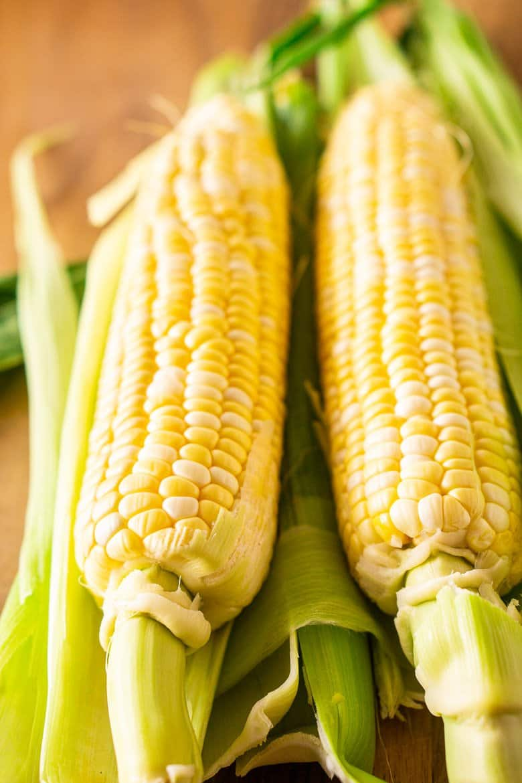 Two ears of corn on a wood cutting board.