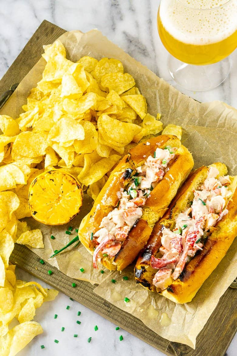 An aerial view of two Maine-style lobster rolls with a pile of chips and a beer.