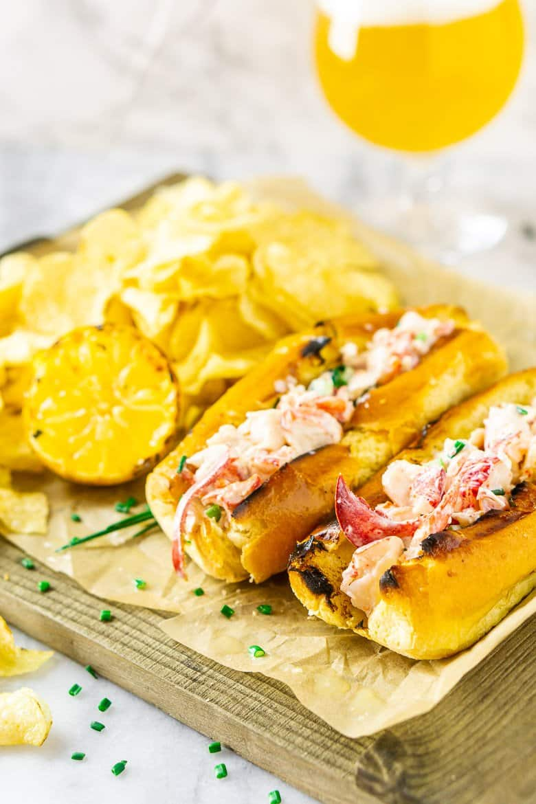 Two Maine-style lobster rolls on parchment paper and a wooden board ready to be served.