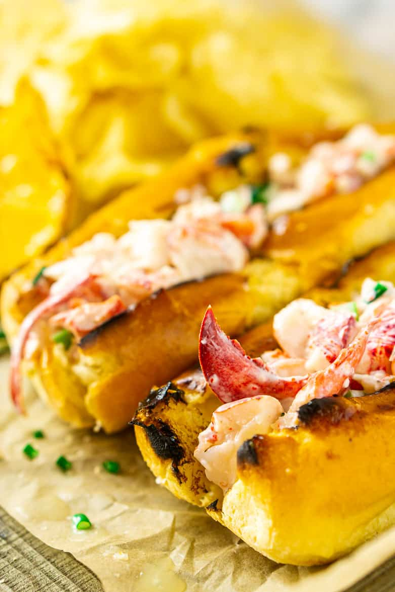 A close-up view of one Maine-style lobster roll with another in the background with chips.