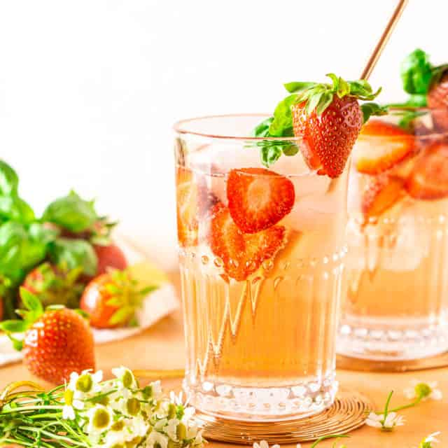 Two strawberry-basil Tom Collins drinks on a pink plank with flowers.
