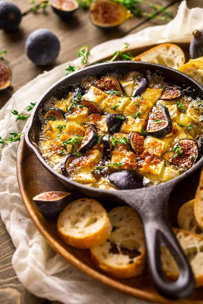 Looking down into a skillet of baked Brie dip with fresh figs and bread.