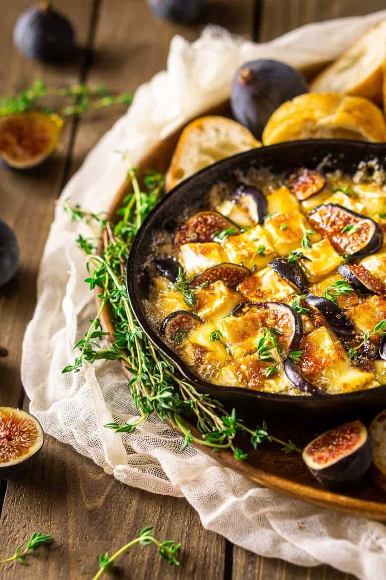 Baked brie with fig and Kahlua sauce with fresh figs and thyme surrounding it.
