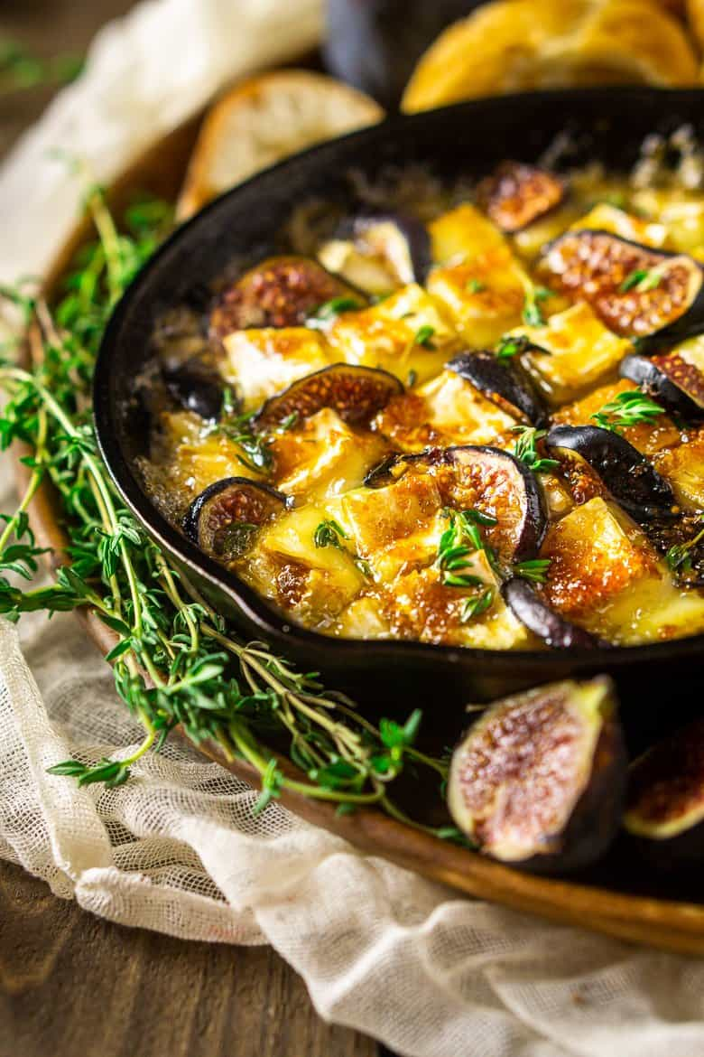 A skillet of baked Brie with fig and fresh thyme.