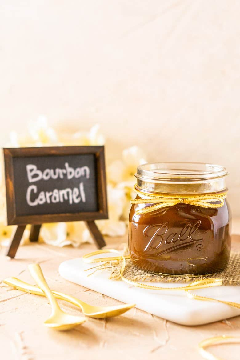 A straight-on shot of bourbon caramel sauce with a chalkboard sign and flowers in the background.