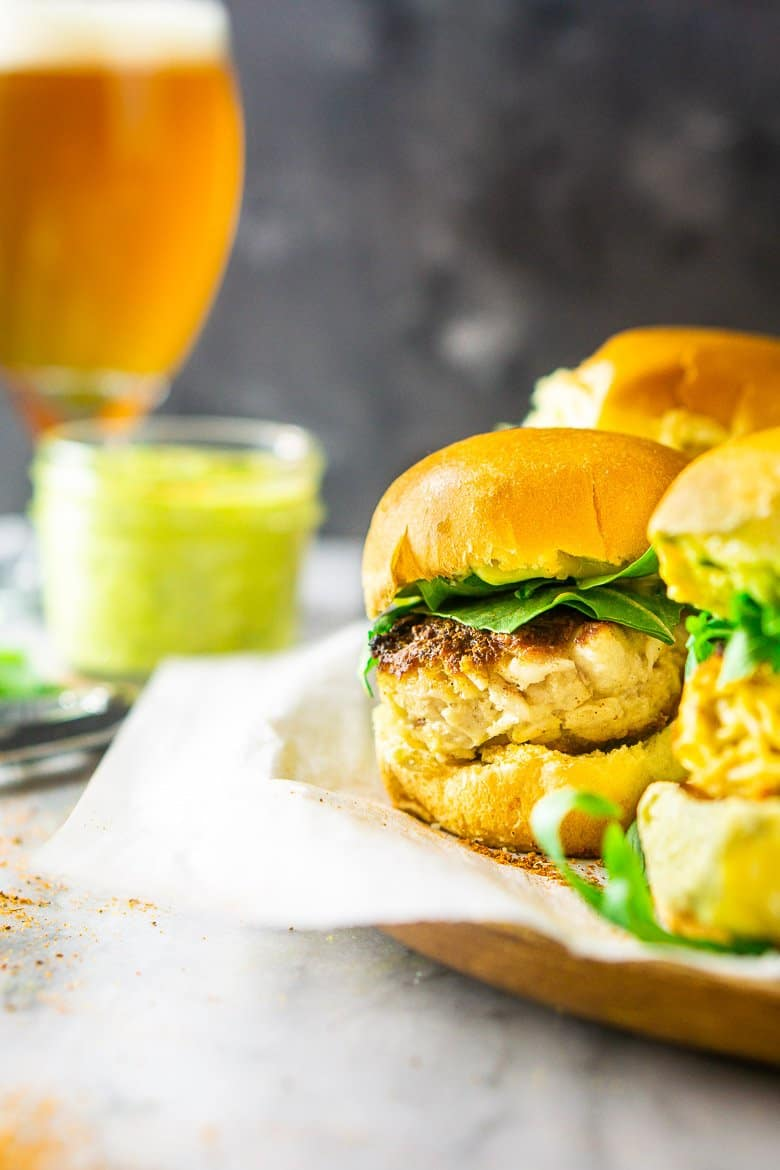 Focusing on one crab cake slider with a beer in the background.