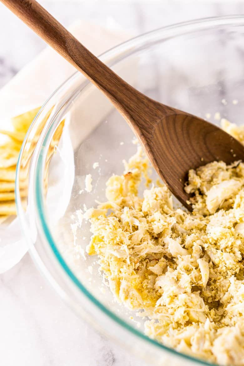 Mixing crushed saltine crackers with crab meat.