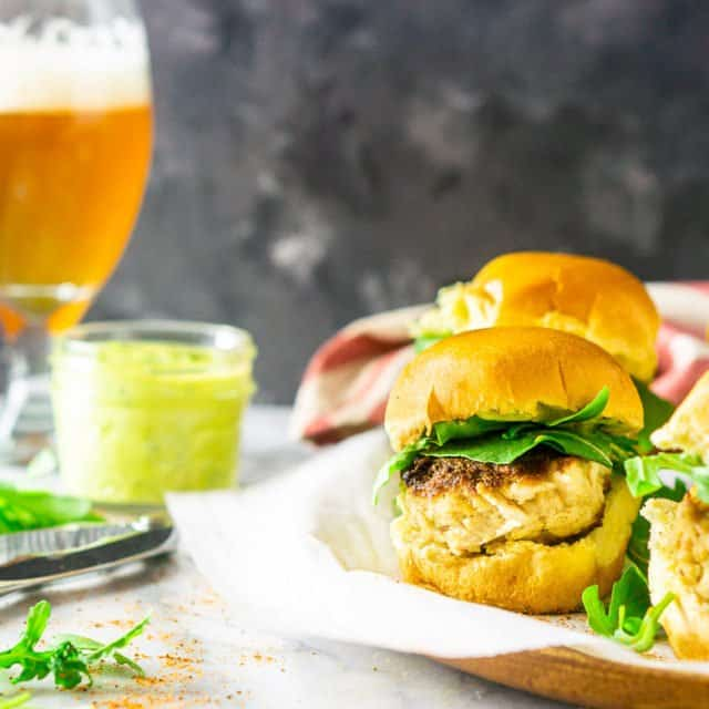 A platter of crab cake sliders with a beer in the background and a mason jar of basil-avocado aioli.