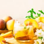 A peach-maple bourbon smash on a wooden tray with a bunch of white flowers.