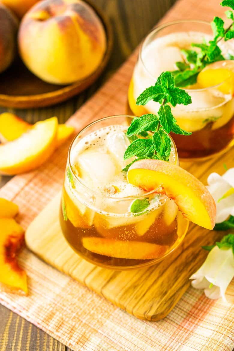 An aerial view looking into a peach-maple bourbon smash with slices of peaches on the side.