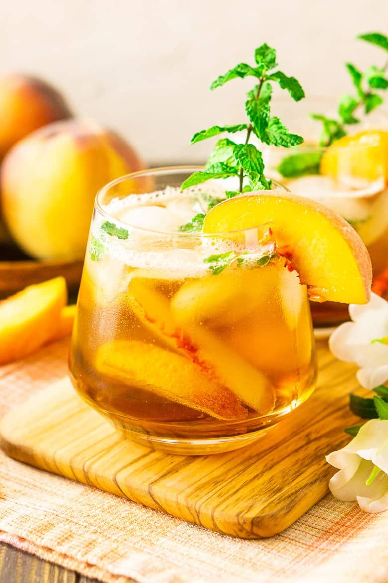 A close-up of a peach-maple bourbon smash with a pile of peaches in the background.