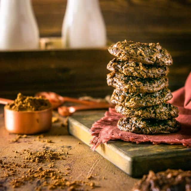 A stack of the best fudgy brownie cookies on a wooden tray with milk bottles.
