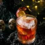 A single Poisoned Orchard Cocktail with steam coming toward you with lights in the background.
