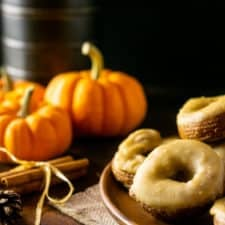 A plate of pumpkin crullers with caramelized maple glaze with pumpkins and fall flowers in the background.
