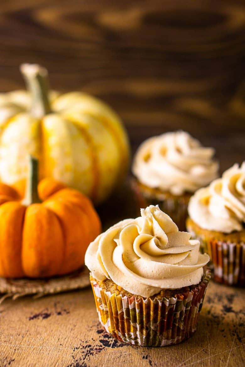 A single brown butter-pumpkin cupcake in front of two pumpkins.
