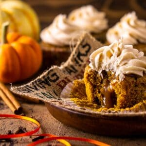 A brown butter-pumpkin cupcake on burlap with an orange ribbon in front of it.