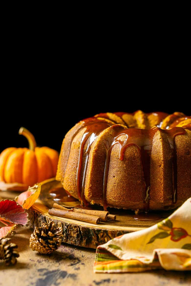 The buttermilk-pumpkin pound cake on a wooden cake stand with a pumpkin in the background and fall-themed napkin.