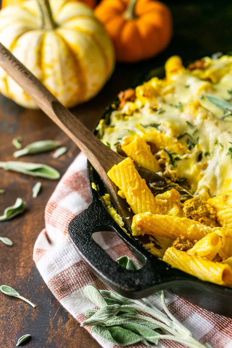 A cast-iron skillet with chorizo and pumpkin baked ziti with a wooden spoon inside and pumpkins in the background.