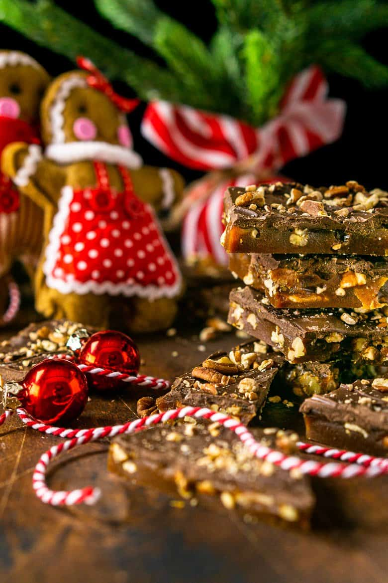 A close-up of the gingerbread toffee in a stack on the side with the gingerbread people in the background..