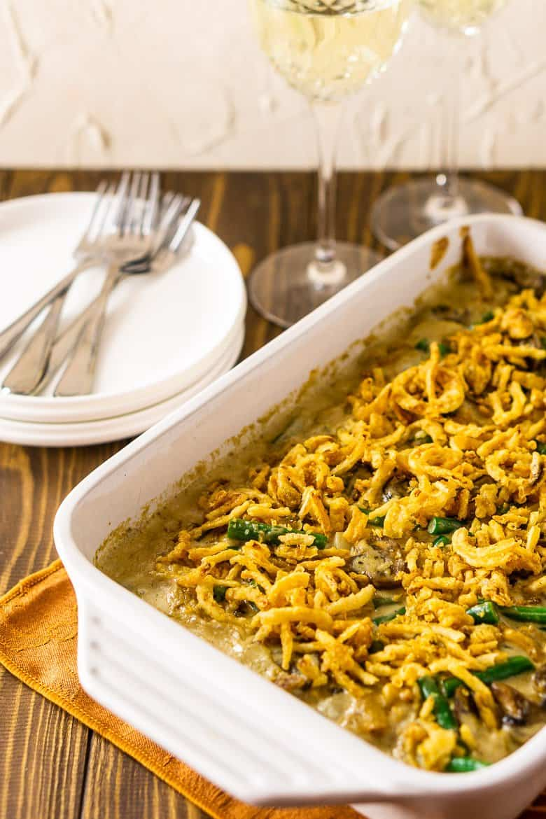 A baking dish filled with homemade green bean casserole on a Thanksgiving-themed napkin with two glasses of wine, a stack of plates and forks.