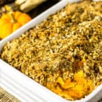 A baking dish of sweet potato souffle with coconut-hazelnut streusel with a pumpkin and Indian corn in the background.