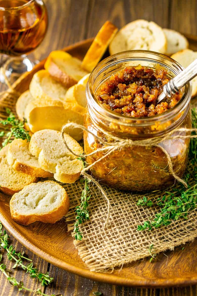 A wooden plate with a mason jar filled with bacon jam surrounded by bread slices, fresh thyme and a glass of bourbon.