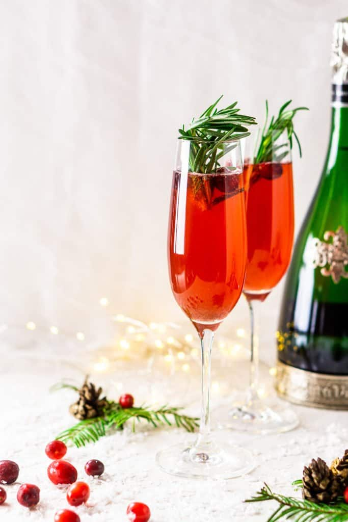 Two cranberry-spice Christmas mimosas with pine needles and cranberries.