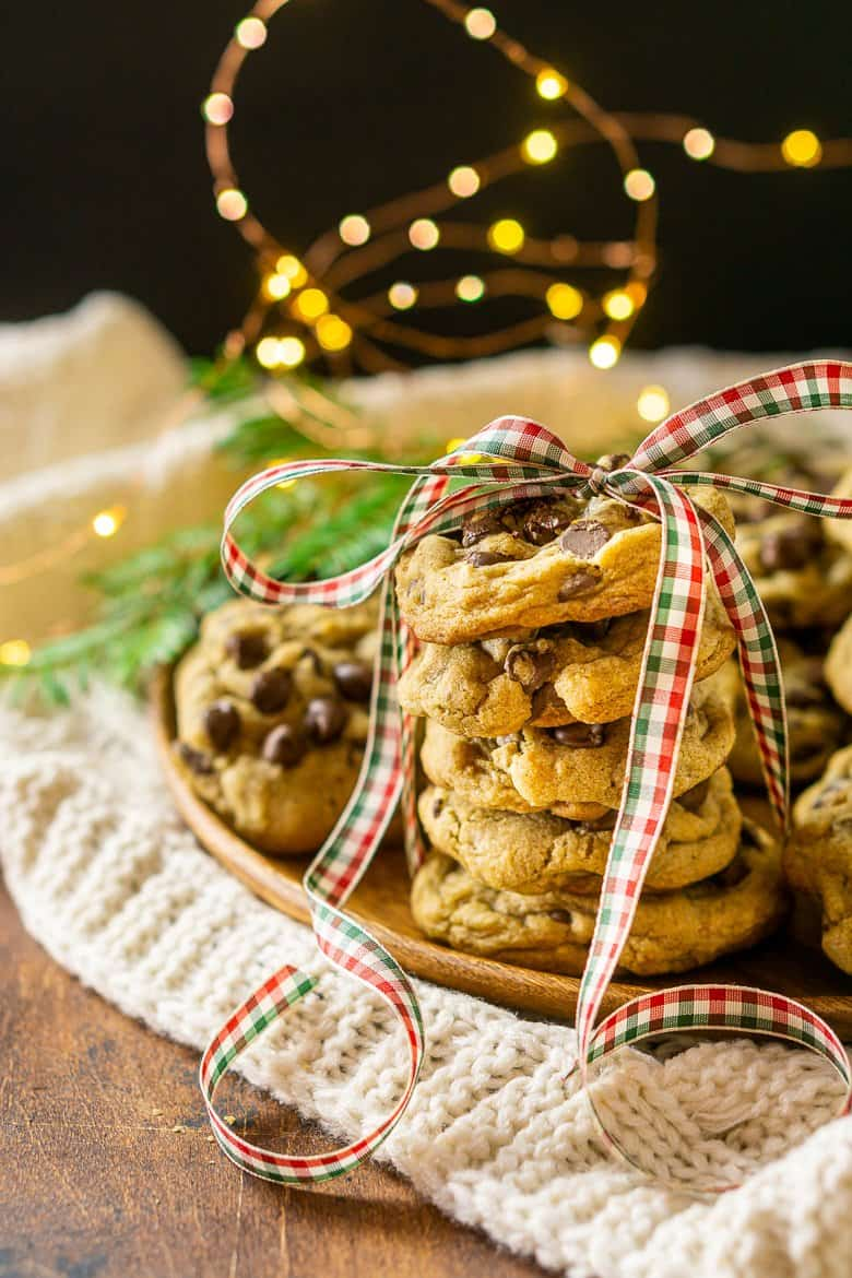 A stack of spiced holiday chocolate chip cookies with a holiday bow and lights in the background.